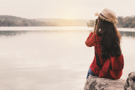 An Asian hipster style woman taking a photo in nature , relaxing time on holiday travel concept