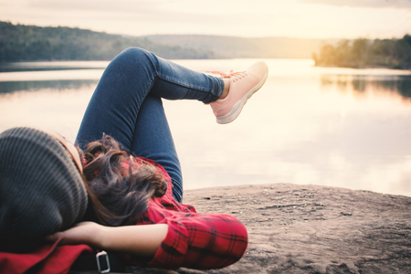 Relaxing moment Asian tourist sleeping on rock waiting for sunset, enjoying time on holiday concept, color of vintage tone