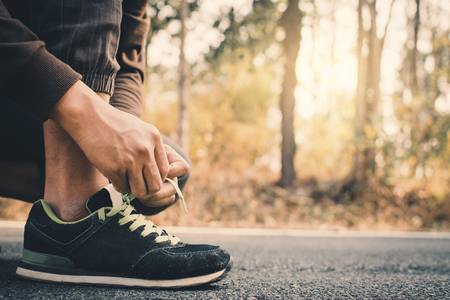Close-up hands of man tying shoelace during running on the road for health, color of vintage tone selective and soft focus Foto de archivo