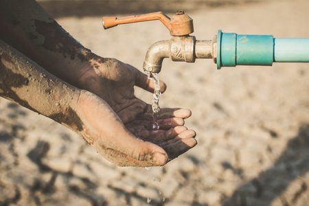 Hand of boy want to drink some water on crack ground. Concept drought and shortage of water crisis Foto de archivo
