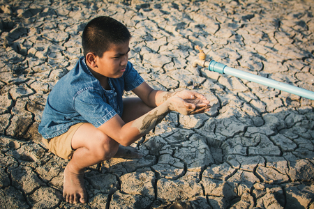 Sad boy want to drink some water on crack ground. Concept drought and shortage of water crisis
