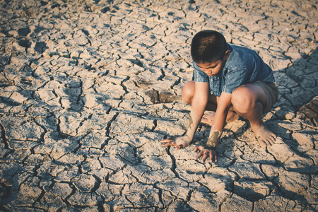 Sad boy sitting on cracked dry ground, drought concept