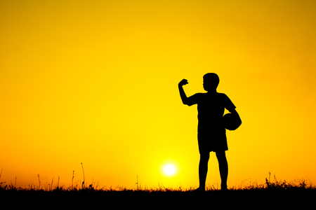 Silhouette of boy playing football during sky sunset background Foto de archivo