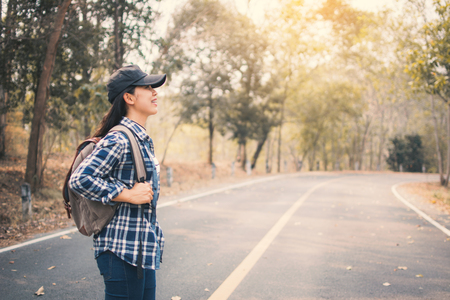 Happy Asian woman backpack in the road and forest background. Relax time on holiday concept travel, color of vintage tone and soft focus