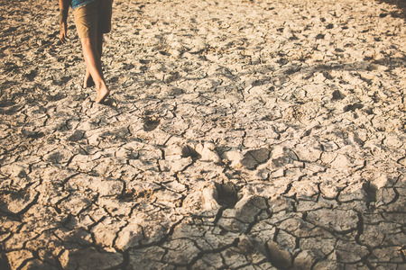Feet of boy walking on cracked dry ground. Hope and drought concept