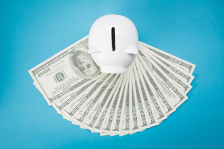 White piggy bank and money on blue background, saving concept