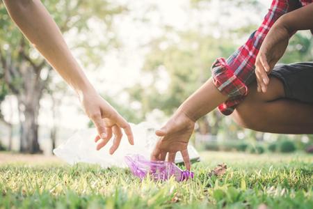 Boy picking up empty of bottle plastic on park ,volunteer concept
