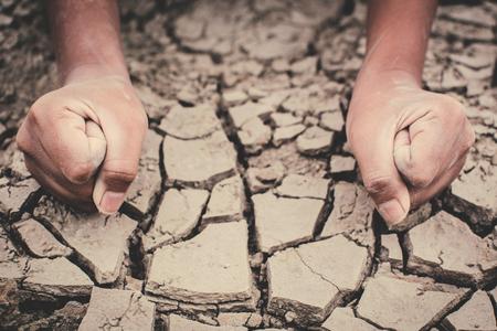 Human hands on cracked dry ground , Concept drought and shortage of water crisis