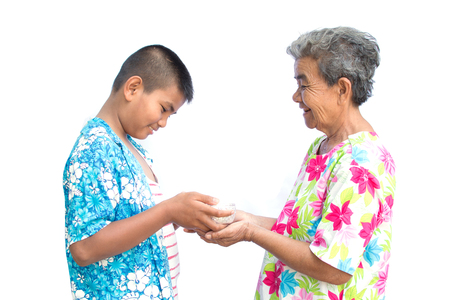 Boy holding bowl of water and flower pour down to old hands woman on white background , Respect concept , Songkran festival in Thailand Reklamní fotografie