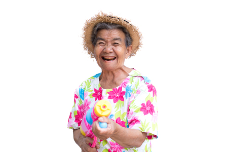 Happy Asian older woman playing water gun on white background, Songkran Festival in Thailand and summer season