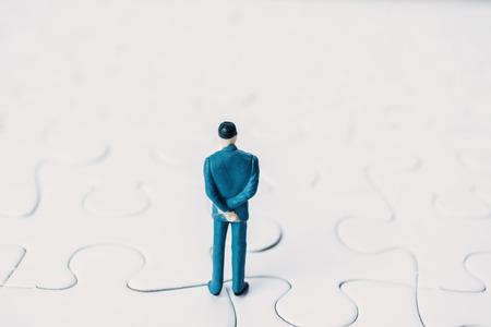 Close up miniature business man standing on white jigsaw, selective and soft focus