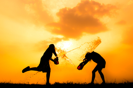 Silhouette of children playing water during sky sunset, Songkran Festival in Thailand and summer season 版權商用圖片