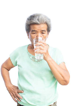 Happy old woman drinking fresh water of glass on white background. Banco de Imagens