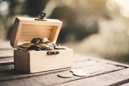 Coins in wood box, color vintage style selective and soft focus. Reklamní fotografie