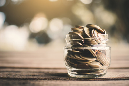 Coins on glass jar on table in nature bokeh background , color vintage style selective and soft focus