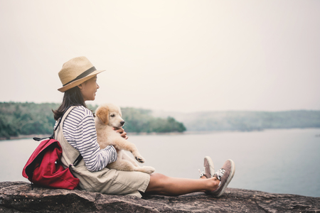 Happy girl playing with little dog in nature background, travel on holiday color of vintage tone and soft focus Reklamní fotografie