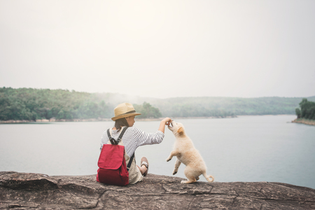 Happy girl playing with little dog in nature background, travel on holiday color of vintage tone and soft focus Banco de Imagens