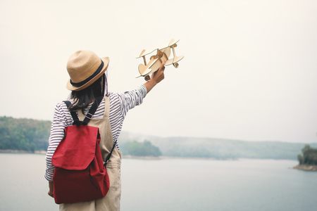 Asian girl playing wooden plane in nature , Relax time on holiday concept travel and freedom,selective and soft focus,tone of hipster style