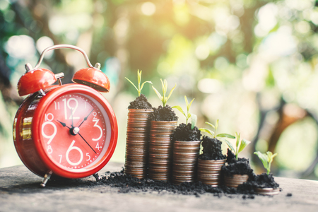 Red alarm clock and coins growing up on table, saving money concept. Banco de Imagens