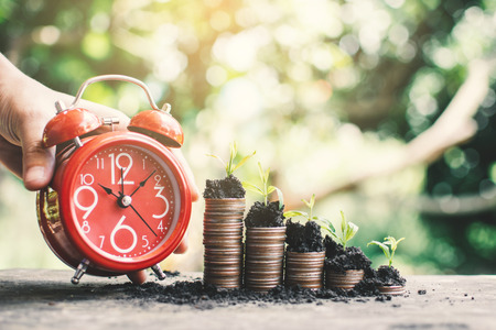 Red alarm clock and coins growing up on table, saving money concept. 版權商用圖片
