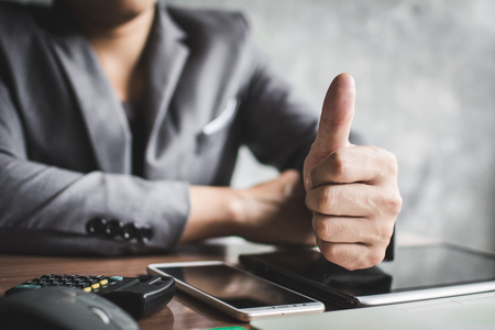 Close up hand of businessman thumb up with confidence on office background