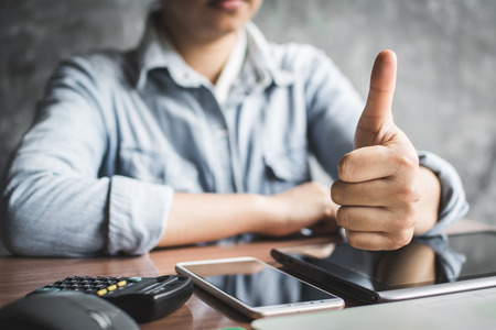 Close up hand of businesswoman thumb up with confidence on office background