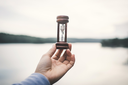 Hand holding hourglass in nature