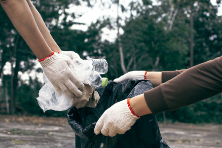 Human hand picking up empty of bottle plastic on park ,volunteer concept