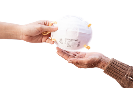 Hand giving a mask for anti pollution in the air. Stock Photo