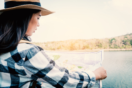 Asian woman looking for destination in a map, backpack on the park journey and traveling on holiday concept.