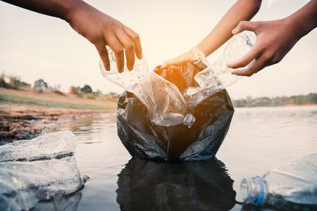 Le volontaire ramassant une bouteille en plastique dans la rivière, protège l'environnement d'un concept de pollution.