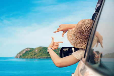Happy woman sitting in the car and traveling summer season on the sea resting and special day to vacation. Stock Photo