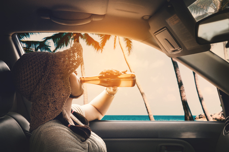 Happy woman sitting in the car and traveling summer season on the sea resting and special day to vacation. Banco de Imagens