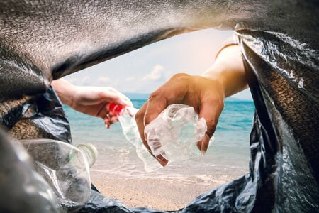 The volunteer picking up a bottle plastic in to a bin bag and the sea background, recycling and protect environment from a pollution concept.