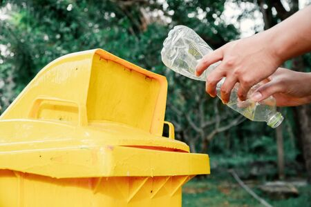 The volunteer picking up a bottle plastic in to a bin , protect environment from a pollution concept.