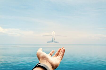 Hand and airplane and sea background, traveling concept. Banco de Imagens