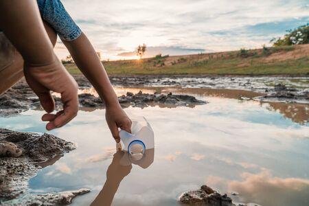 Garçon écopant de l'eau du lac, de la sécheresse et du réchauffement climatique. Banque d'images