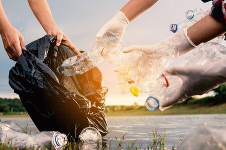 Der Mensch, der eine Plastikflasche im Fluss aufhebt, schützt die Umwelt vor einem Wasserverschmutzungskonzept.