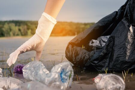 Human picking up a bottle plastic in the river, protect environment from a water pollution concept.