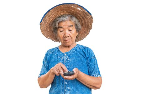 Happy old farmer woman holding a calculator on a white background. Calculate income and expenses concept.