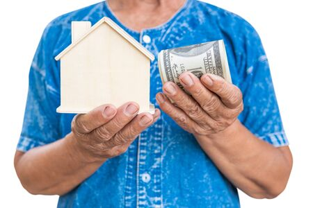 Old farmer woman holding little wood house on a white background. housing and land concept. Banco de Imagens