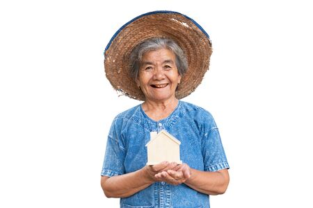 Happy old farmer woman holding little wood house on a white background.