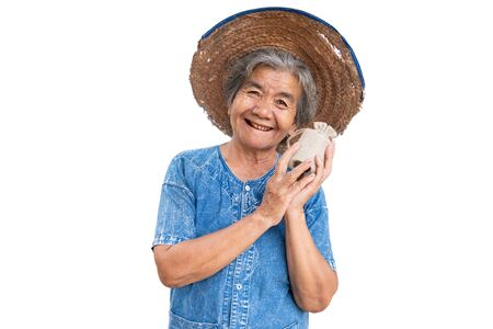Happy old farmer woman holding a money bag on a white background. Imagens