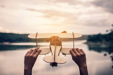 Hand holding wood airplane in the nature background, freedom to travel concept. Stok Fotoğraf