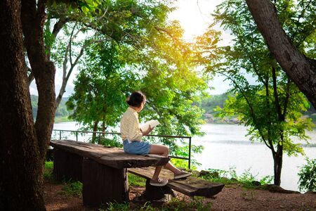 Asian girl reading a book during hobby time. Imagens