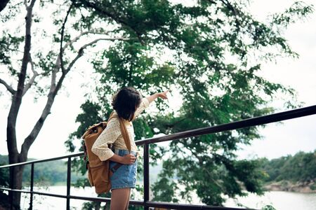 Asian girl backpack on the park background, journey and traveling on holiday concept. Imagens