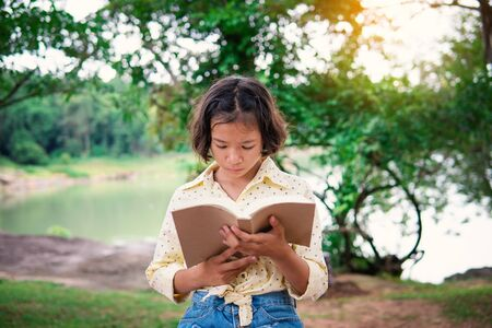 Asian girl reading a book during hobby time. Stok Fotoğraf