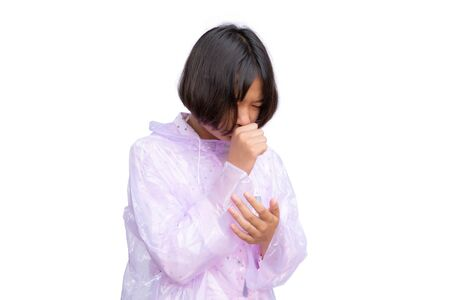 Cute Asian girl in raincoat coughing on the white background. Stok Fotoğraf