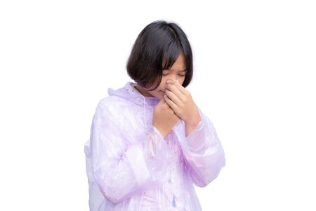 Cute Asian girl in raincoat coughing on the white background. Imagens