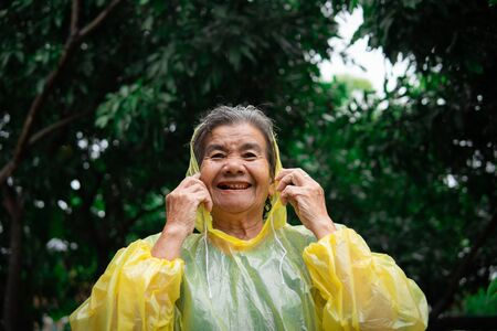 Happy old woman in raincoat during the rainfall. Stok Fotoğraf